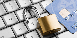 Lock down your PCI data and avoid a costly breach as represented hear by a padlock on a keyboard.