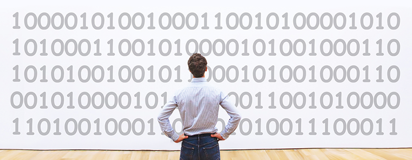 Man standing in front of binary artwork in a museum, considering what file encryption software should include
