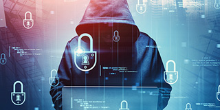 Ominous hooded figure standing over a laptop. New cybersecurity risks in tech today.