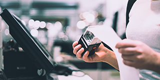 Woman holds receipt at a cash register, working to stay PCI compliant